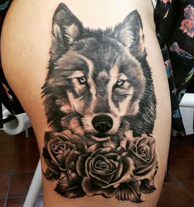 lobo y rosas en la pierna mujer