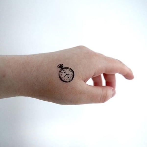 tatuaje pequeño y simple de reloj en la mano