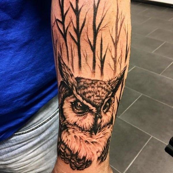 tattoo de buho y bosque en el brazo