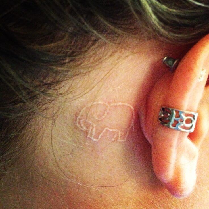 tatuaje de elefante en color blanco detras de la oreja