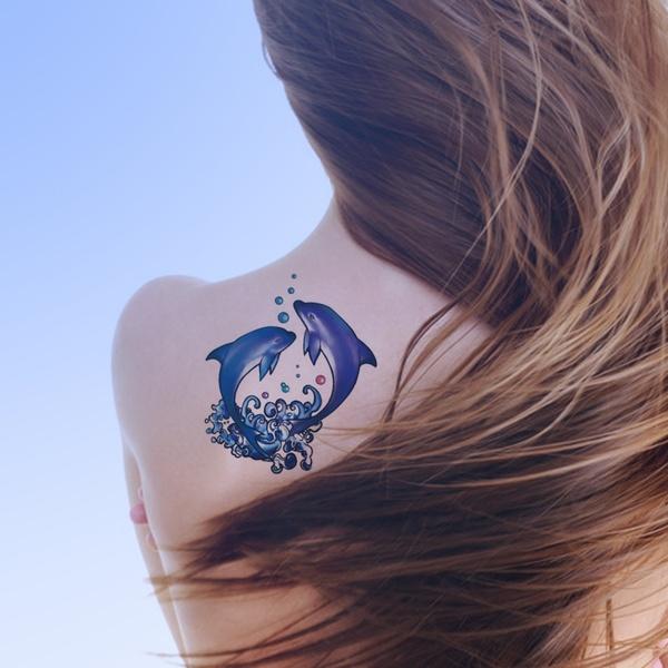 hermoso tatuaje de delfines en el homoplato