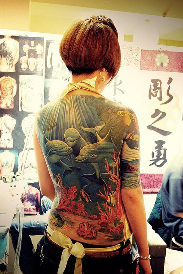 increible tatuaje de delfines en la espalda