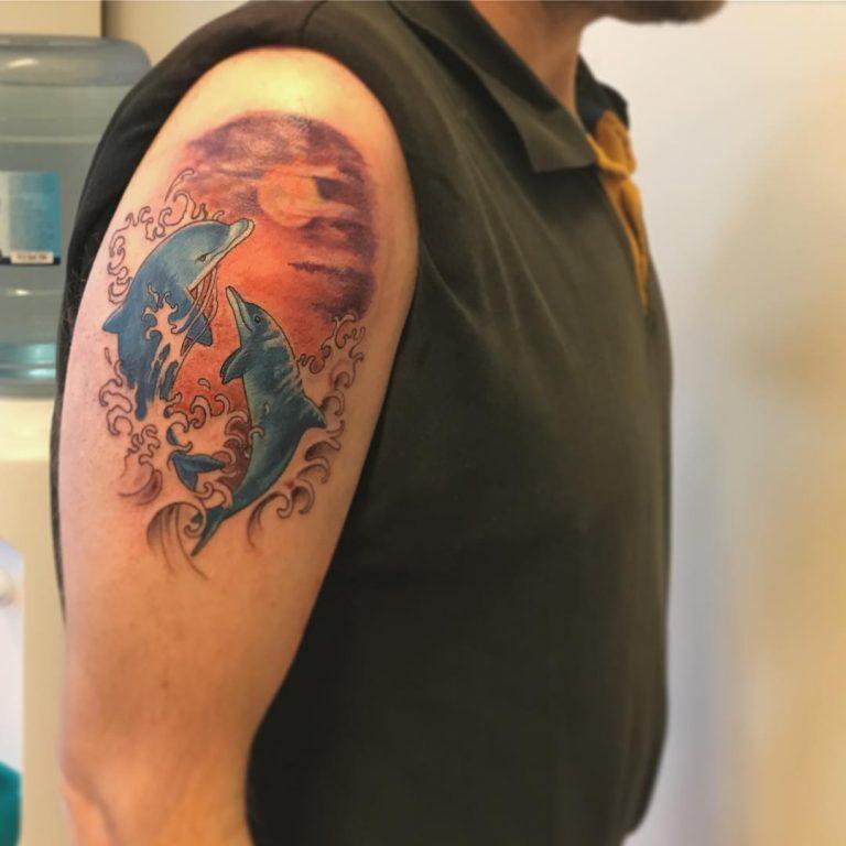 tattoo de delfines saltando del agua