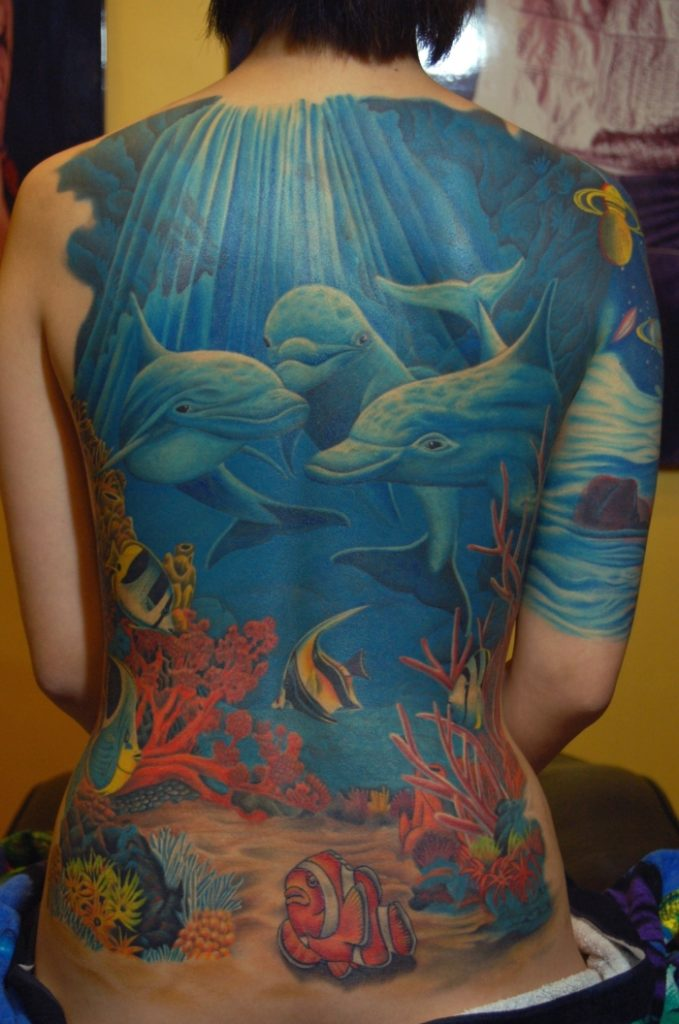 tatuaje de delfines en el mar en la espalda a color