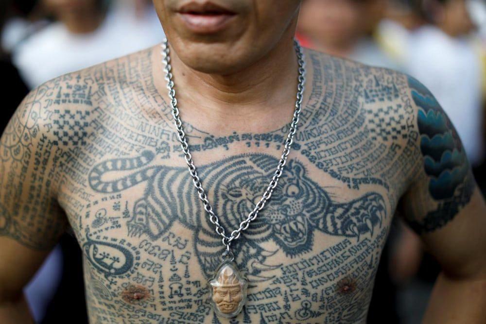 tatuaje de tigre e inscripciones en tailandes hombre