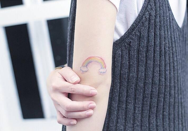 tatuaje de arcoiris en la parte de atras del brazo