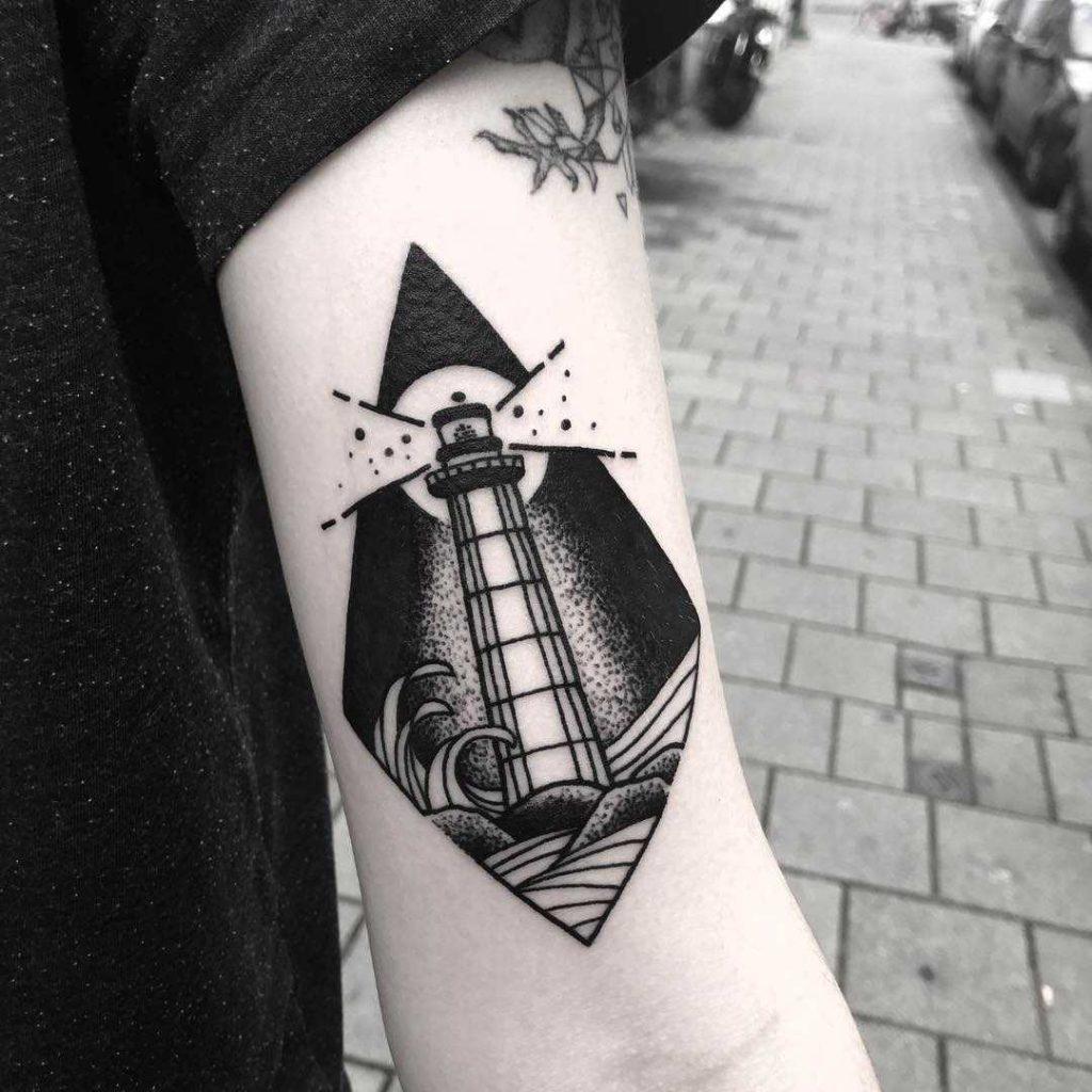 tatuaje de faro gris y negro en el brazo