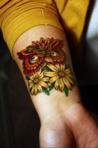 buho y girasoles en el brazo mujer