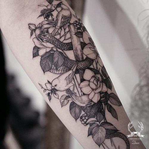 tattoo de serpiente y aves en el brazo