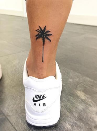 tatuaje de palmera en la pantirrilla