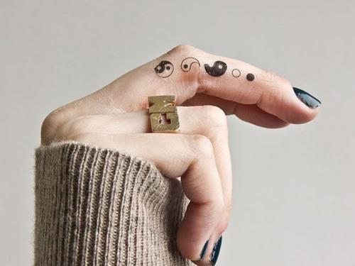 tatuaje de yin yang pequeño en el dedo