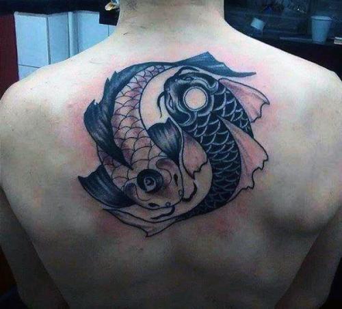 tatuaje yin yang con peces en la columna