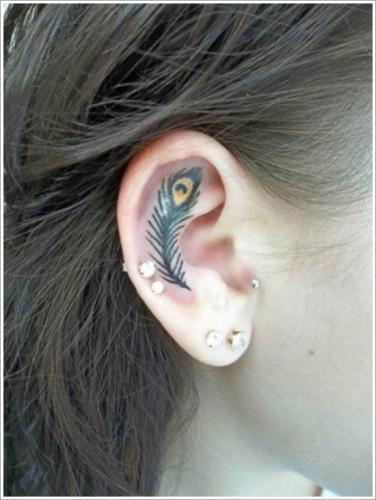 tatuajes de pluma en el interior de la oreja