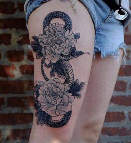 vibora y flores en la pierna mujer